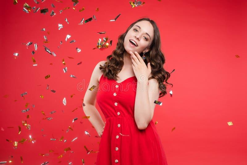 Wspaniała brunetki dziewczyna w czerwieni sukni w confetti zdjęcie stock