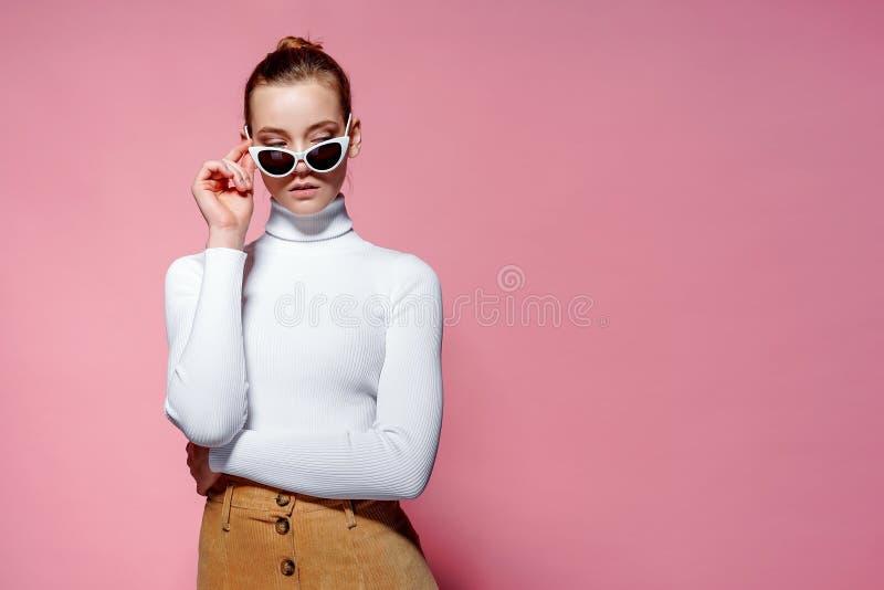 Wspaniała elegancka kobieta w biel dziającym golfie i okulary przeciwsłoneczni pozuje nad menchii ścianą zdjęcie stock