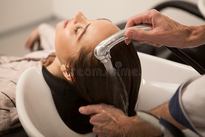 Wspaniała kobieta ma jej włosy myjącego fryzjerem obrazy stock