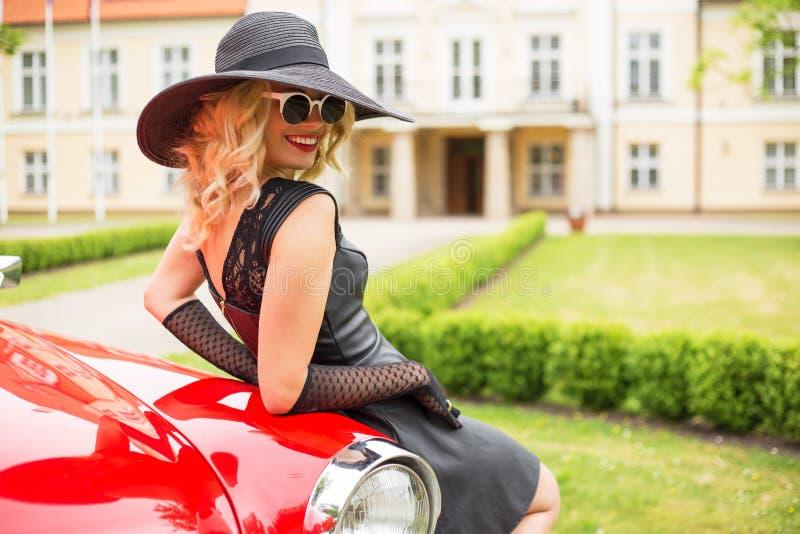 Wspaniała kobieta opiera przeciw retro samochodowi zdjęcia royalty free
