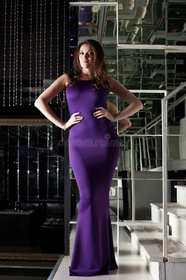 Wspaniała kobieta pozuje w długiej purpury sukni obraz royalty free