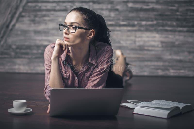 Wspaniała kobieta używa laptop na podłoga fotografia stock