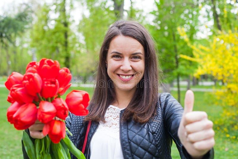 Wspaniała kobieta z czerwonymi tulipanami w parku fotografia stock