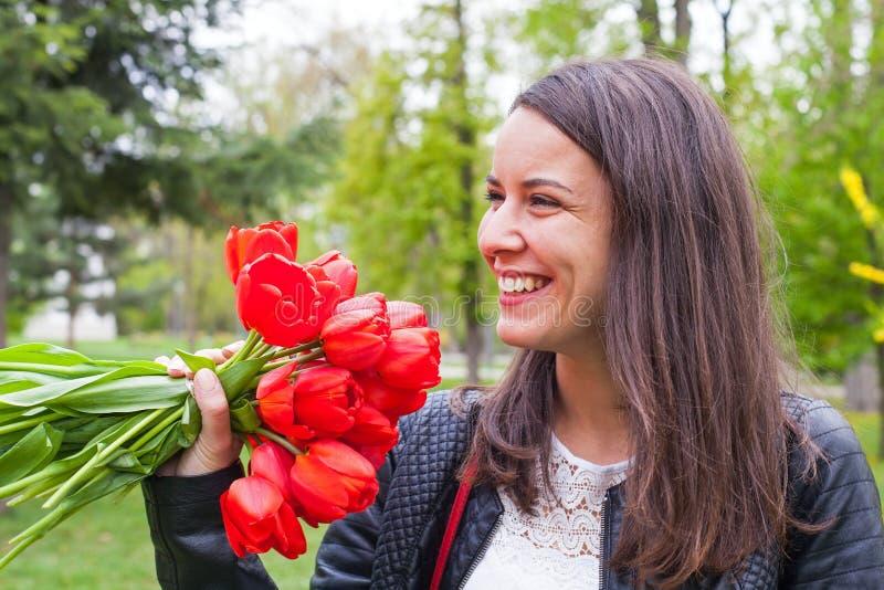 Wspaniała kobieta z czerwonymi tulipanami w parku zdjęcia stock
