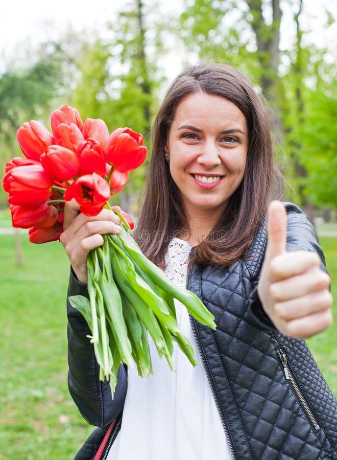 Wspaniała kobieta z czerwonymi tulipanami w parku obrazy stock
