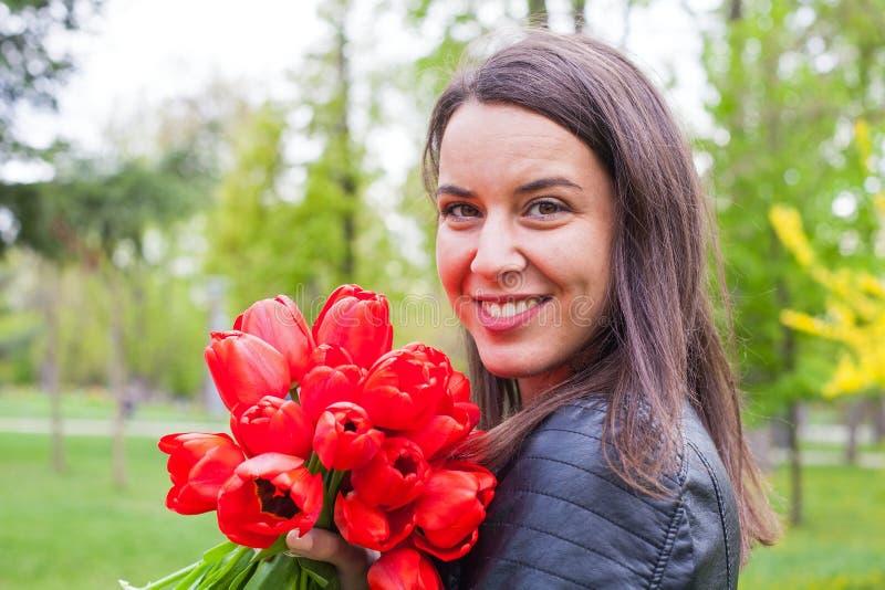 Wspaniała kobieta z czerwonymi tulipanami w parku zdjęcie royalty free
