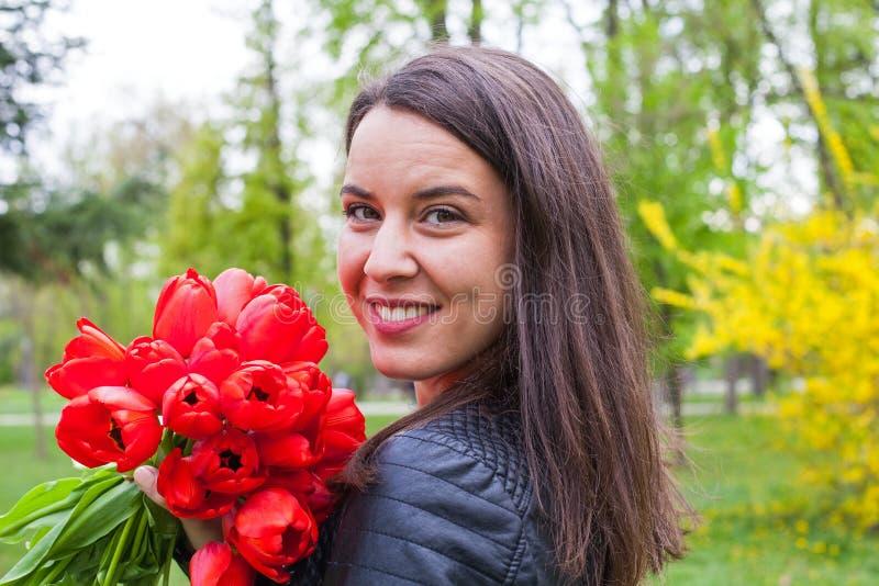 Wspaniała kobieta z czerwonymi tulipanami w parku zdjęcia royalty free