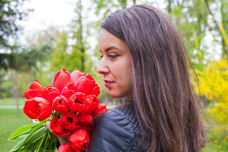 Wspaniała kobieta z czerwonymi tulipanami w parku fotografia royalty free