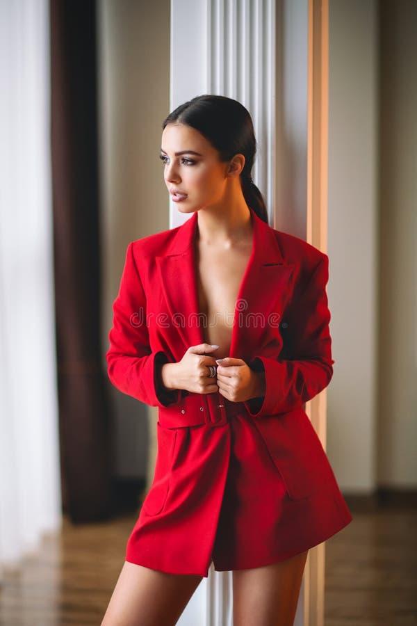 Wspaniała kobiety brunetka jest ubranym czerwoną kurtkę zdjęcie royalty free