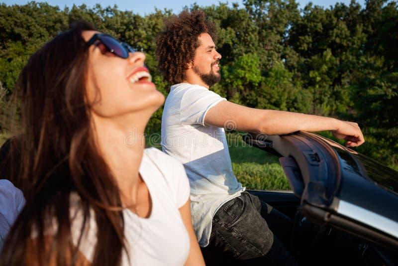 Wspaniała młoda ciemnowłosa kobieta w okularach przeciwsłonecznych z kędzierzawym młodym człowiekiem jest siedząca i ono uśmiecha obrazy stock
