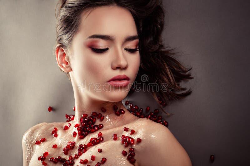 Wspaniała młoda dziewczyna z różowym makijażem z granatowów ziarnami fotografia royalty free
