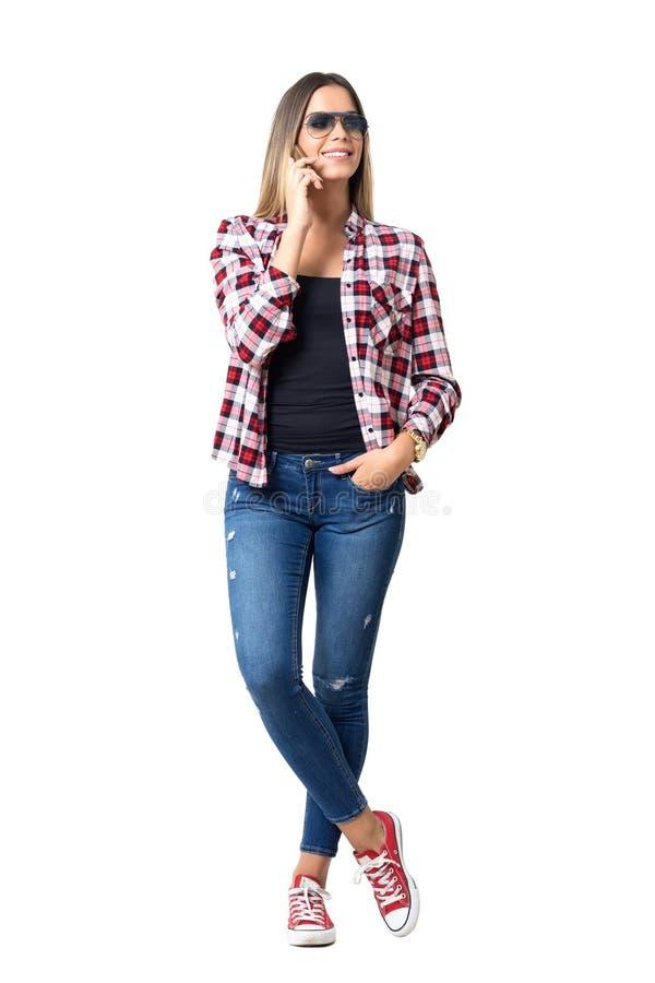 Wspaniała młoda kobieta patrzeje daleko od ono uśmiecha się z okularami przeciwsłonecznymi na telefonie zdjęcia royalty free