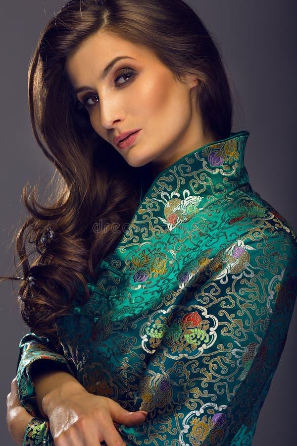 Wspaniała młoda kobieta patrzeje w zielonej japońskiego stylu kurtce obrazy royalty free