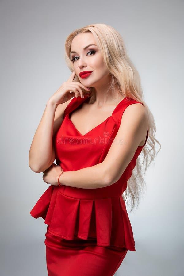 Wspaniała młoda kobieta w czerwieni sukni na szarym tle zdjęcie royalty free