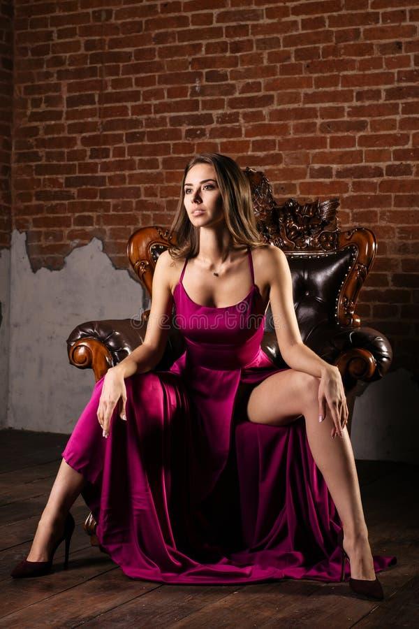 Wspaniała młoda kobieta w luksusowej sukni a siedzi nogi w krześle w luksusowym mieszkaniu oddzielnie obraz stock