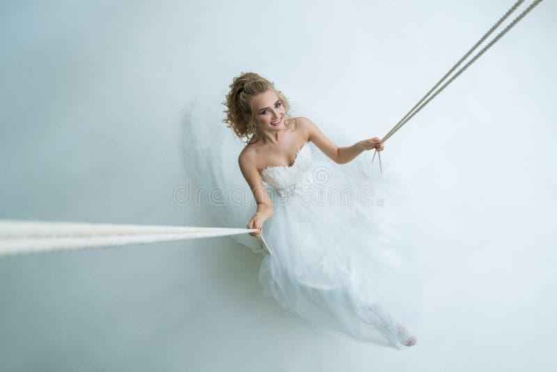 Wspaniała młoda panna młoda na huśtawce w studiu fotografia royalty free
