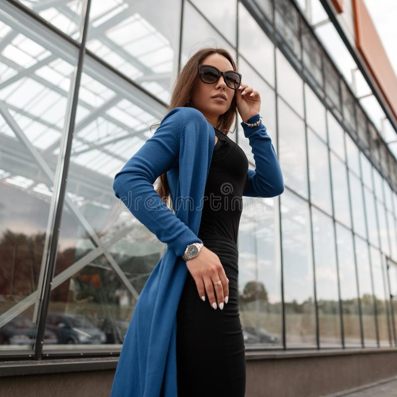 Wspaniała modniś młoda kobieta w rocznika długim trykotowym przylądku w cajgach w koszulce w modnych okularach przeciwsłonecznych obraz royalty free