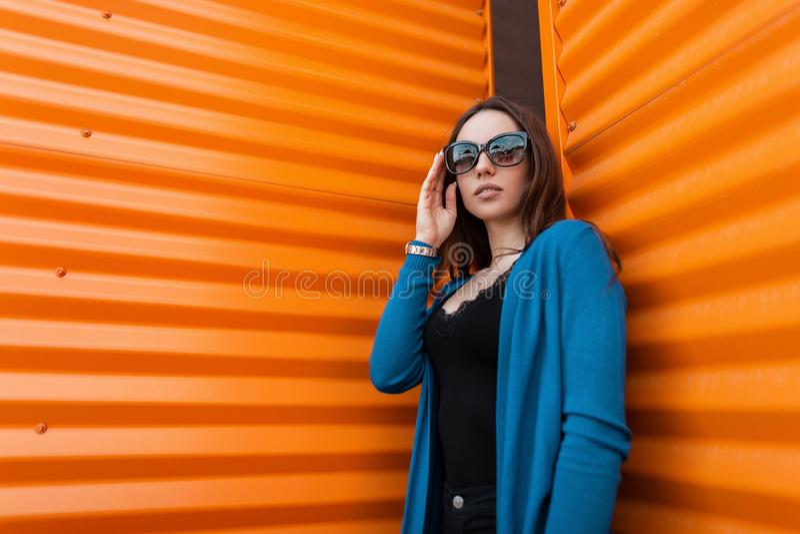 Wspaniała piękna młoda modniś kobieta w eleganckim błękitnym trykotowym przylądku w czarnej koszulce w modnych okularów przeciwsł obraz royalty free
