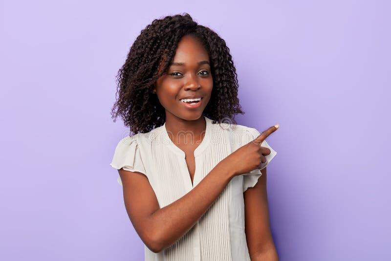 Wspaniała powabna afro dziewczyna wskazuje z jej palcem w białej eleganckiej bluzce zdjęcie royalty free