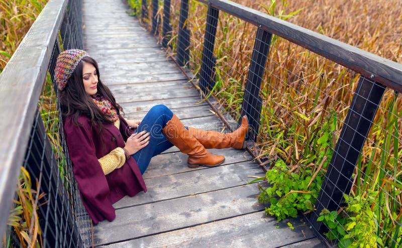 Wspaniała romantyczna młoda kobieta z pięknym długim brązu włosy, siedzi na drewnianym moście w ładnym jesień stroju, pa zdjęcia royalty free