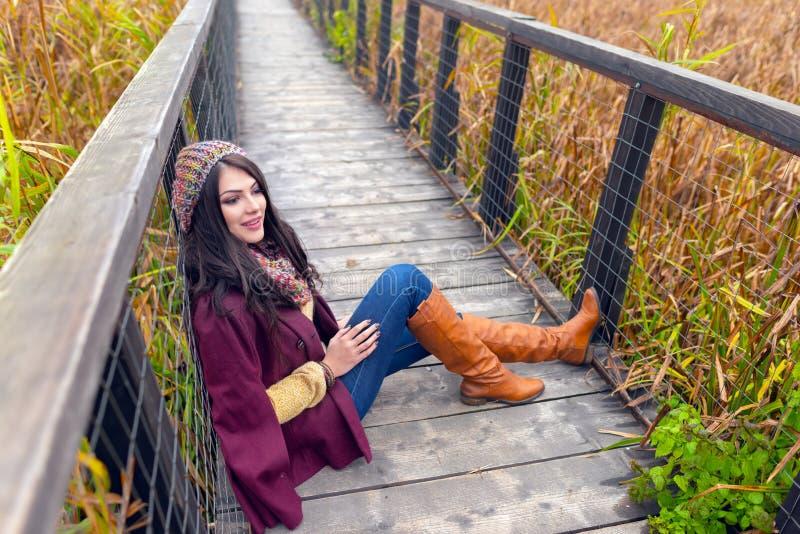 Wspaniała romantyczna młoda kobieta z pięknym długim brązu włosy, siedzi na drewnianym moście w ładnym jesień stroju, zdjęcia royalty free