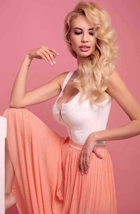 Wspaniała seksowna kobieta z blond kędzierzawym włosy w eleganckiej sukni posin zdjęcie stock