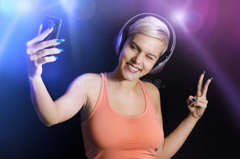 Wspaniała szczęśliwa młoda dziewczyna w świetlicowym bierze selfie fotografia stock