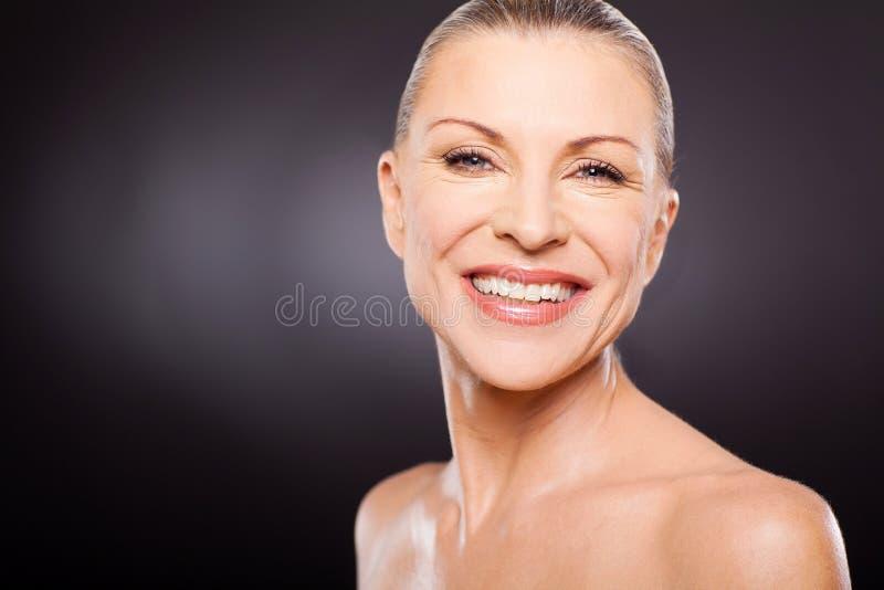 W połowie pełnoletni kobiety ono uśmiecha się fotografia stock