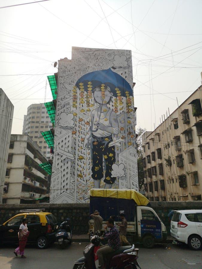 Wspaniałe graffiti sztuki ulicznej chłopca schroniącego się pod parasolem w Mahim East Mumbai fotografia stock