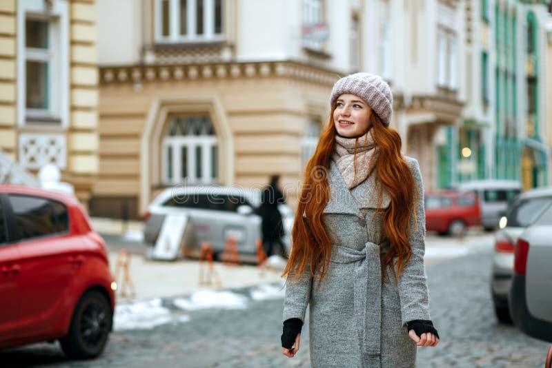 Wspaniałej czerwieni głowy zimy wzorcowa jest ubranym nakrętka i żakiet pwalking fotografia stock