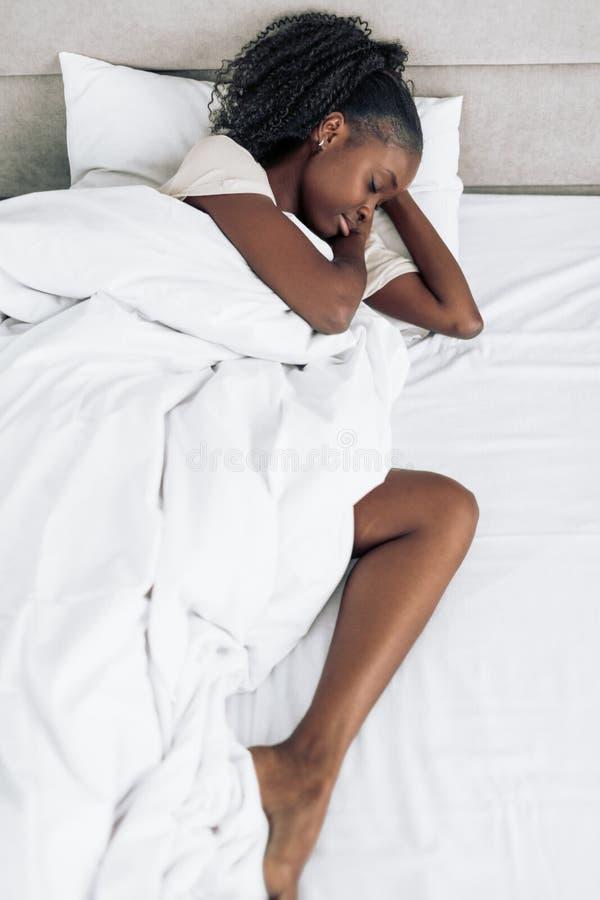 Wspaniały afrykański dziewczyny dosypianie w jej łóżku przy nocą zdjęcia stock