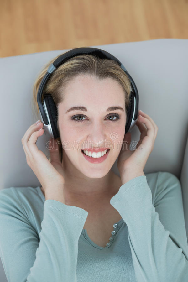 Wspaniały młodej kobiety słuchanie z hełmofonami muzyczny ono uśmiecha się przy kamerą obraz stock