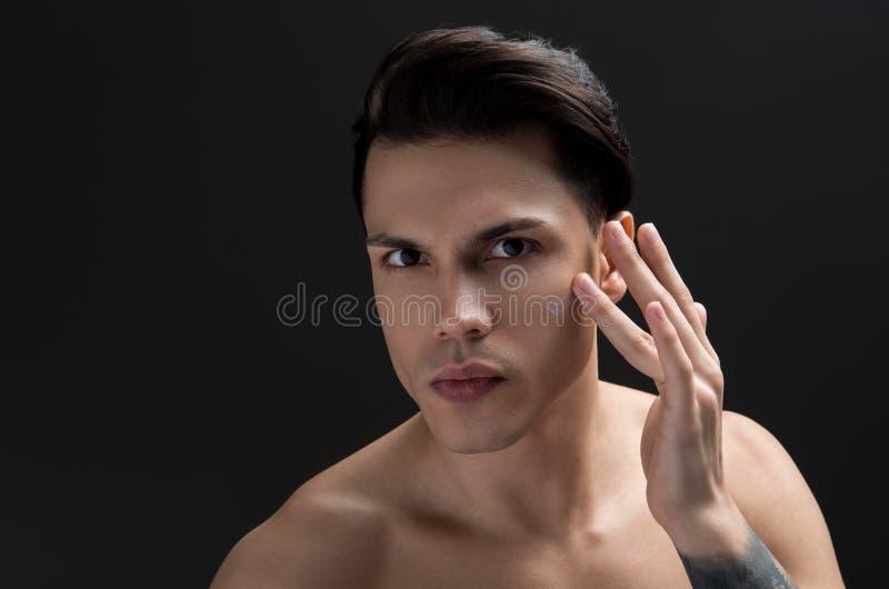 Wspaniały młody facet stosuje starzenie się śmietankę na jego skórze zdjęcia stock