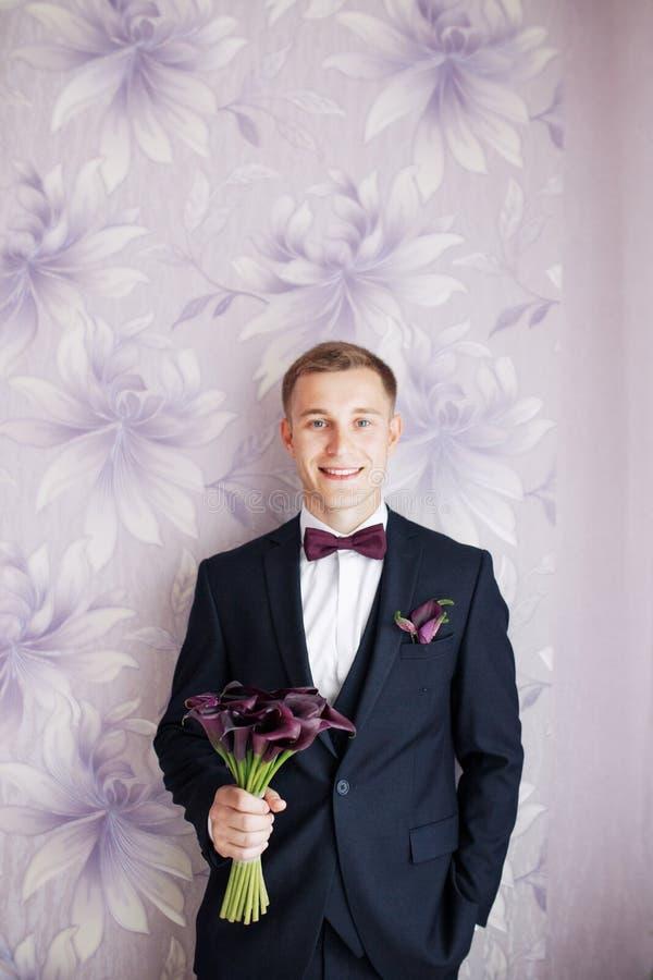 Wspaniały uśmiechnięty fornal Przystojny fornal uśmiecha się panny młodej i czeka przy ślubnym smokingiem Elegancki mężczyzna w c zdjęcia stock