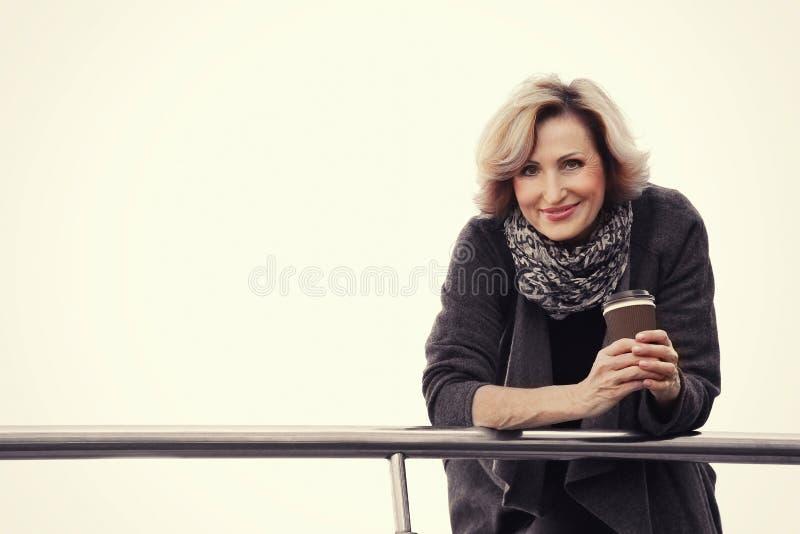 Wspaniały w średnim wieku bizneswoman z filiżanką kawy pozuje na miastowym tle obrazy royalty free