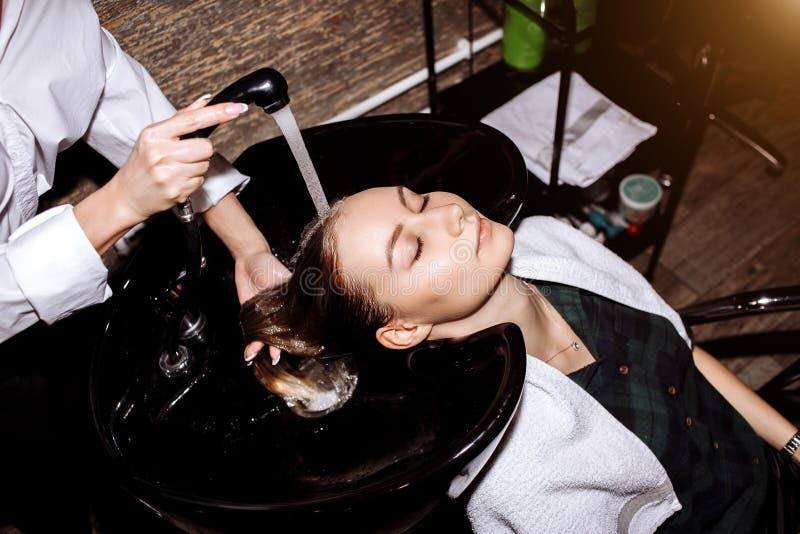 Wspania?a ?liczna m?oda kobieta cieszy si? kierowniczego masa? podczas gdy fachowy fryzjer stosuje szampon jej w?osy Zamyka w g?r zdjęcie royalty free