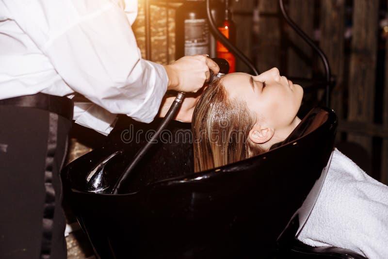 Wspania?a ?liczna m?oda kobieta cieszy si? kierowniczego masa? podczas gdy fachowy fryzjer stosuje szampon jej w?osy Zamyka w g?r obraz stock