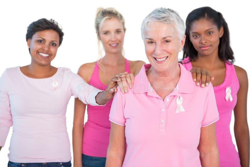 Wspierająca grupa kobiety jest ubranym menchia wierzchołki i nowotworów piersi faborki obraz royalty free
