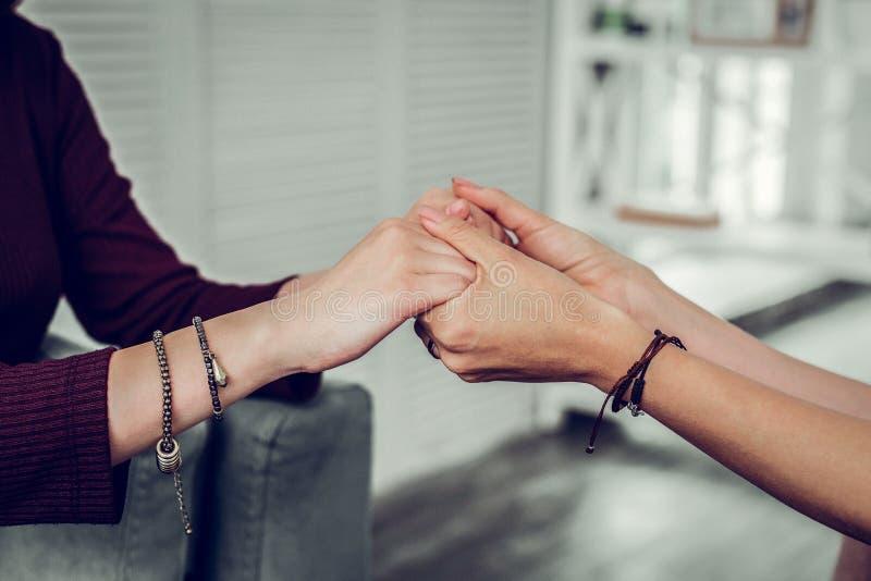 Wspierający psycholog jest ubranym bransoletki trząść ręki klient obraz stock