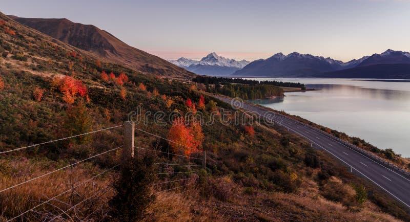 Wspina się kucbarskiego punkt widzenia z jeziornym pukaki i drogą prowadzi góra kucharza wioska Brać podczas jesieni w Nowa Zelan fotografia stock