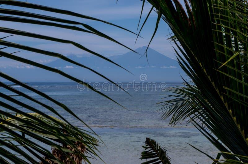 Wspina się Rinjani przez drzewek palmowych strzelających od Sumbawa z widokiem w kierunku Lombok fotografia royalty free