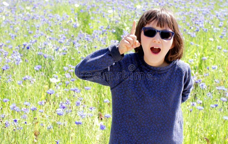Wstrząśnięty ekspresyjny dziecko z okularami przeciwsłonecznymi nad pogodną chabrową łąką, plenerową obrazy royalty free