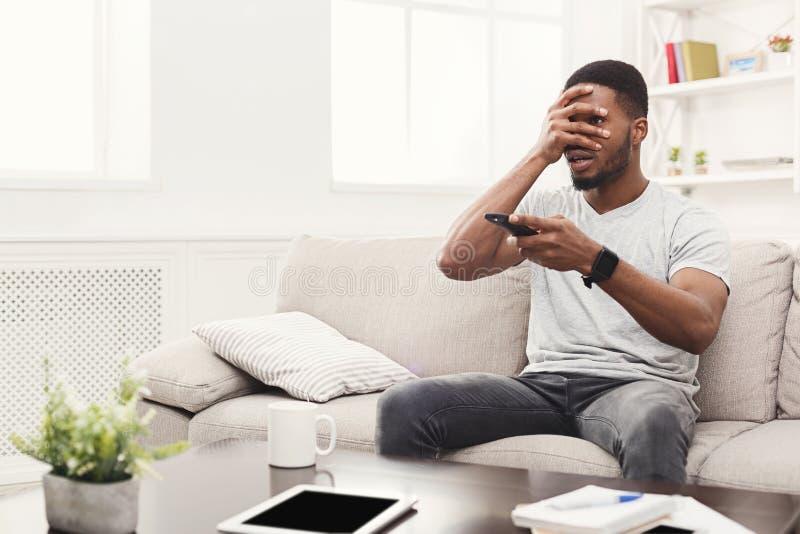 Wstrząśnięty młody afroamerykański mężczyzna wathing tv w domu obrazy royalty free