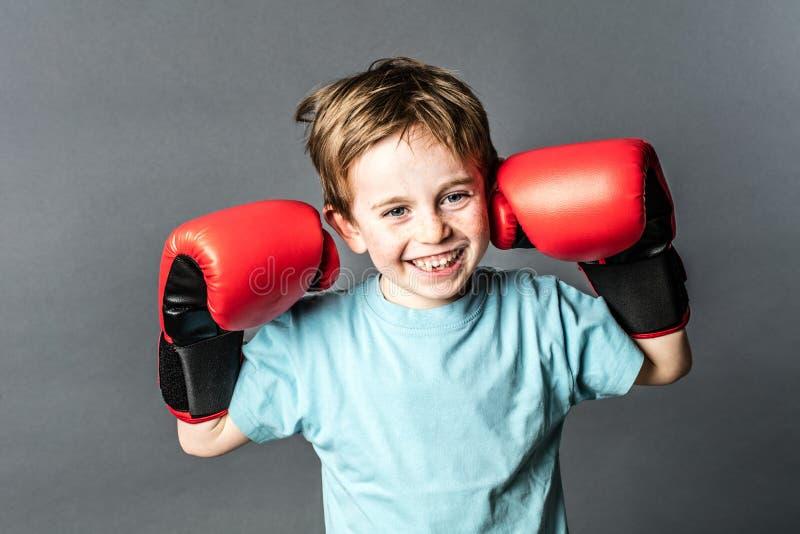 Wstrząśnięty młody chłopiec chichotanie z bokserskimi rękawiczkami up dla walki obrazy stock