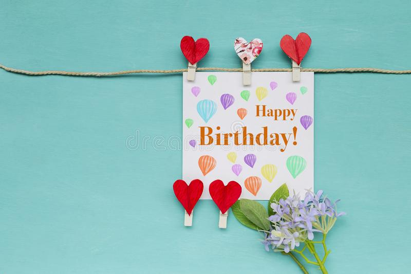 Wszystkiego najlepszego z okazji urodzin karta z czerwoną kierową klamerką i purpury kwitniemy obraz royalty free
