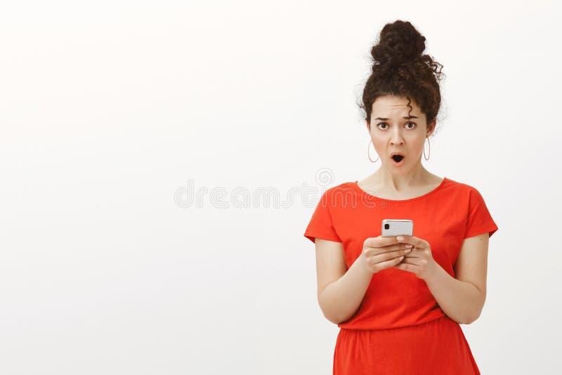 Wtf, der diese Mitteilung schrieb Porträt des entsetzten missfallenen reizend weiblichen Mädchens im roten Kleid, fallender Kiefe stockfotos