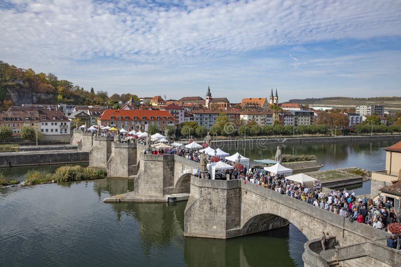 People visit old bridge over river Main in Wuerzburg, Germany. WUERZBURG, GERMANY - OCT 6, 2018: people visit old bridge over river Main in Wuerzburg, Germany royalty free stock image