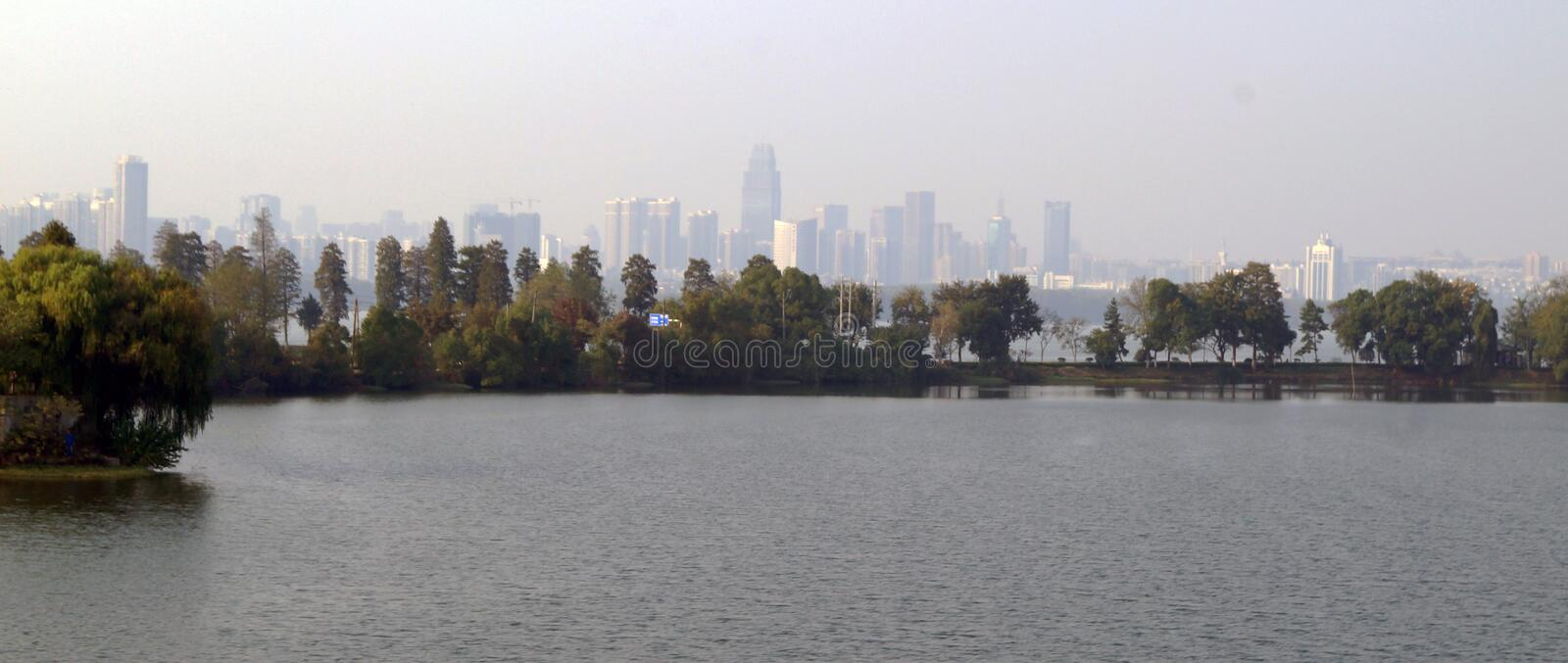 Wuhan China in the back. View of the chinese city of Wuhan in Hubei province, panoramic view of a lake, trees and the tall buildings of the city in the royalty free stock photography