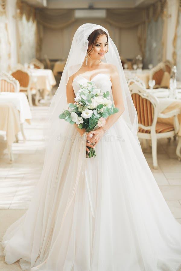 Wunderbare Braut mit einem luxuriösen weißen Kleid und einem Blumenstrauß lizenzfreies stockfoto