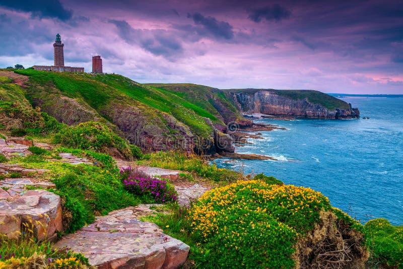 Wunderbare felsige und blumige Küstenlinie mit Leuchtturm, Kappe Frehel, Frankreich lizenzfreie stockbilder